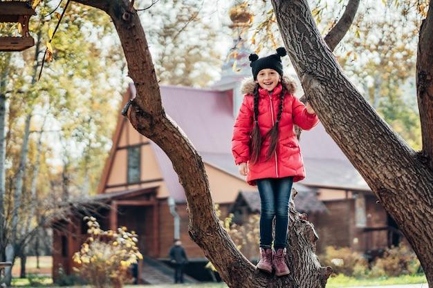La bambina si arrampica su un albero Foto Gratuite