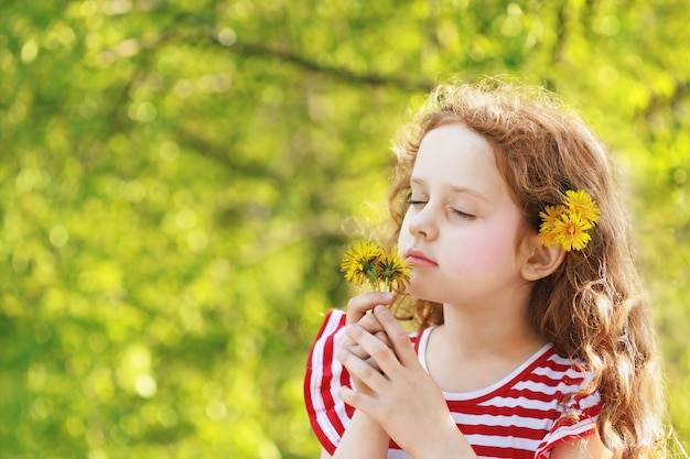 Little girl closed her eyes and breathes yellow dandelions in the field. Premium Photo