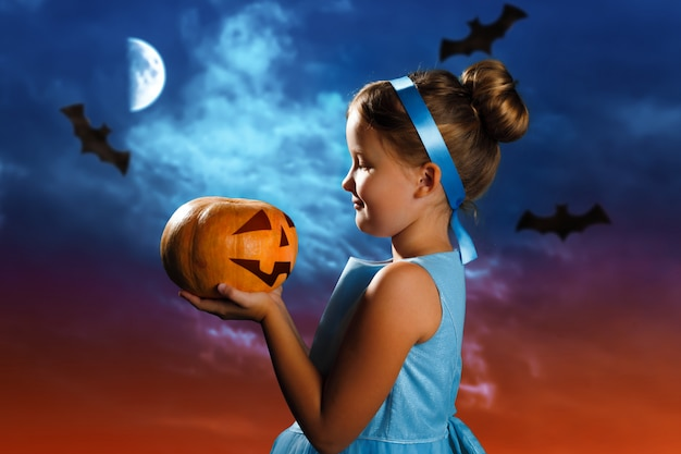 Little girl in a costume of the cinderella holds a pumpkin on the background of the evening moon sky. Premium Photo