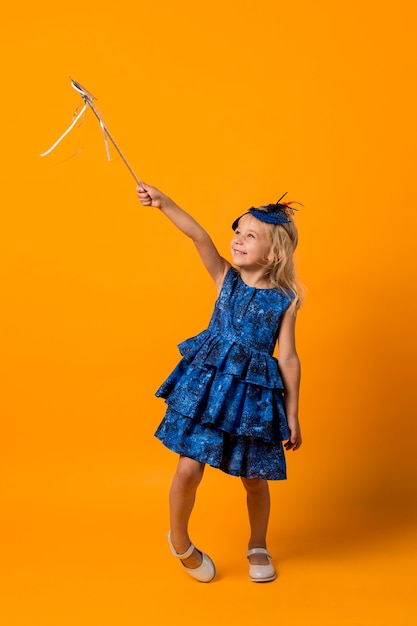 Little girl in costume with wand and mask Free Photo