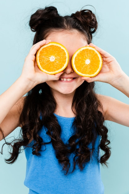 Little girl covering eyes with orange slices Free Photo