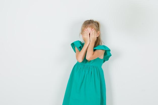 緑のドレスを着て手で顔を覆い、恥ずかしがり屋に見える少女。正面図。 無料写真