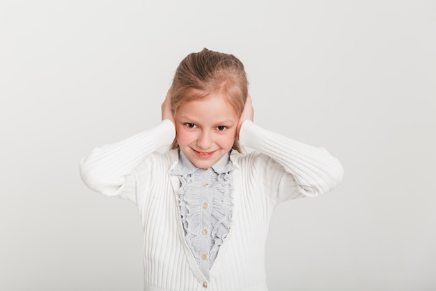 Little girl covering her ears Free Photo
