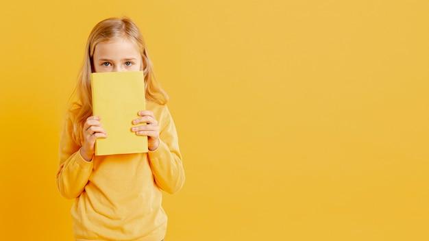 本で彼女の顔を覆っている小さな女の子 Premium写真