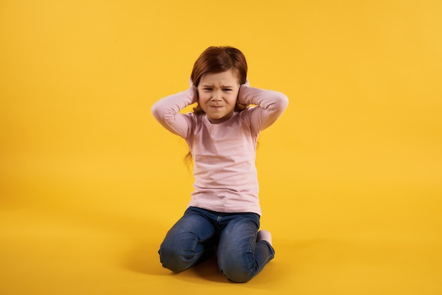 Little girl covers ears. extremely loud. Premium Photo