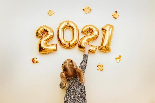 어린 소녀는 황금 숫자로 집의 벽을 장식합니다. 프리미엄 사진