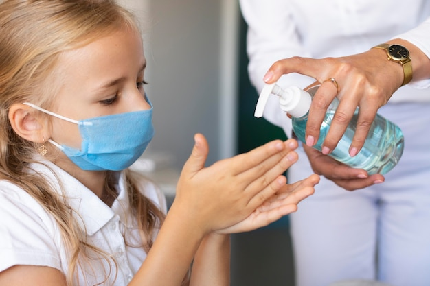 Bambina che disinfetta le sue mani Foto Gratuite