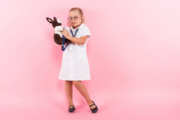Little girl in doctor costume with toy Premium Photo