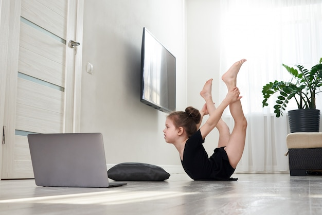 Little girl doing gymnastics exercises at home using online learning with laptop computer, internet education concept Premium Photo