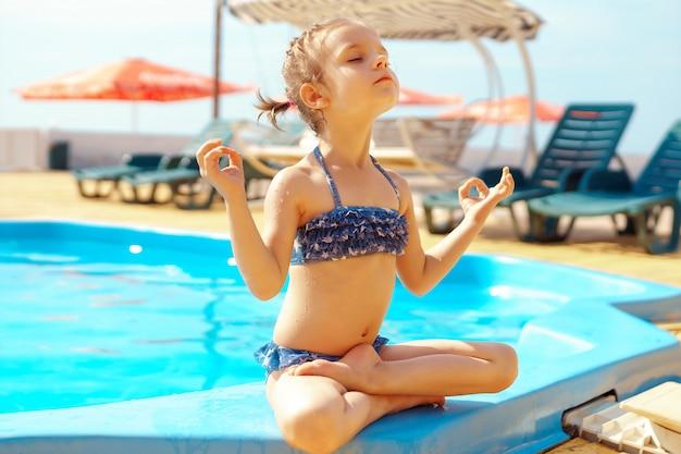 Little girl doing yoga at beach Premium Photo