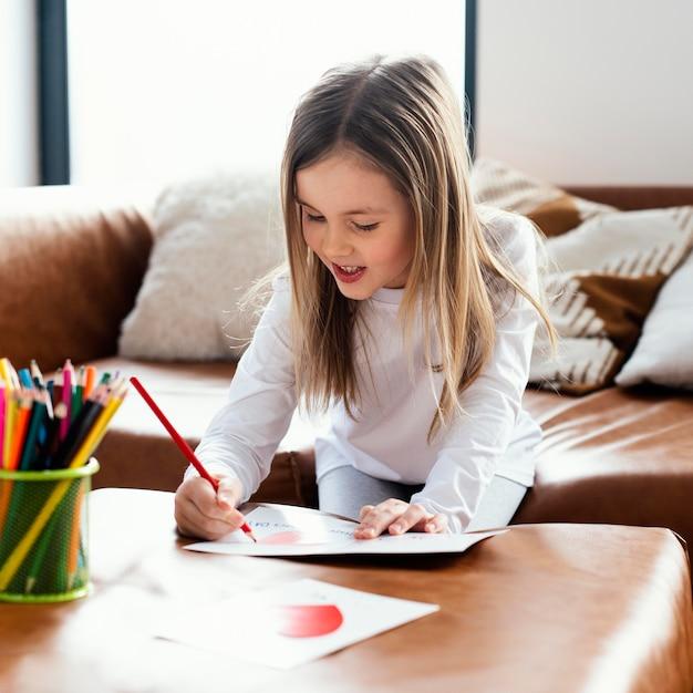 Маленькая девочка рисует открытку на день отца в качестве сюрприза для папы Бесплатные Фотографии