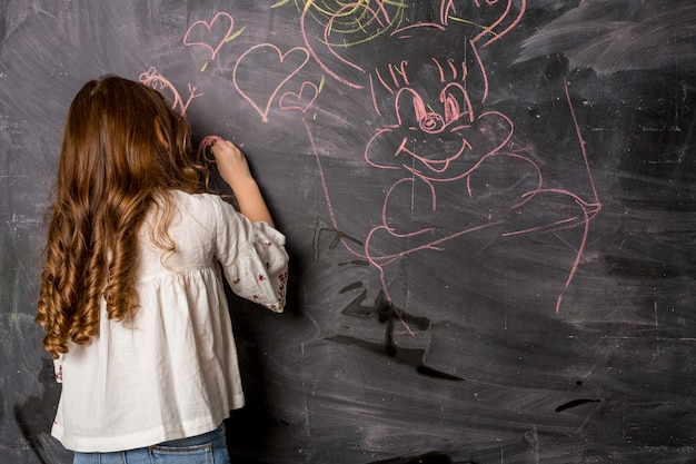 Little girl drawing on blackboard Free Photo