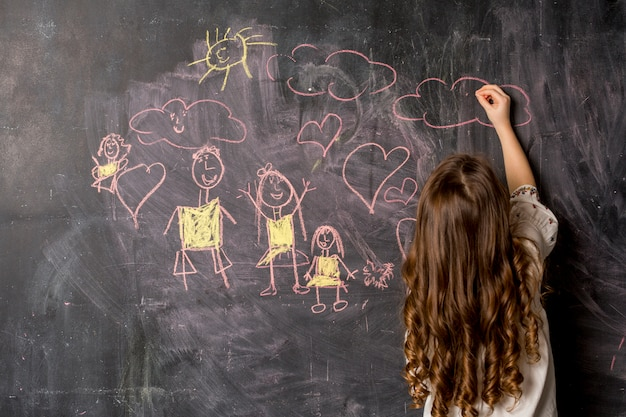 Little girl drawing family on blackboard Free Photo