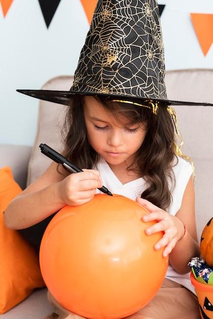 Little girl drawing a halloween baloon Free Photo