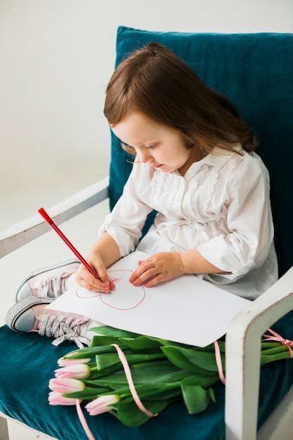 Little girl drawing heart on paper sheet Free Photo