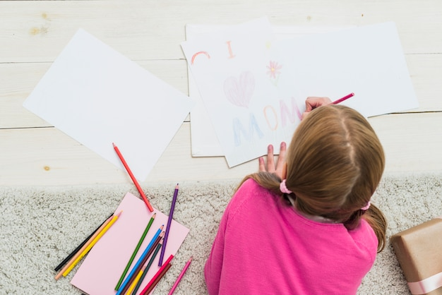 Little girl drawing i love mom on paper Free Photo