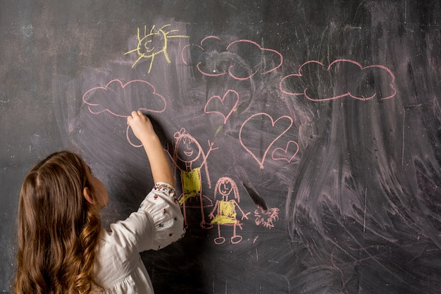 Little girl drawing mother and daughter on blackboard Free Photo
