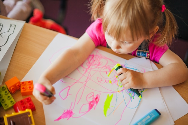 Little girl drawing with marker pens Free Photo