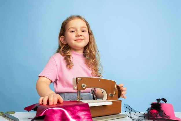 Little girl dreaming about future profession of seamstress Free Photo