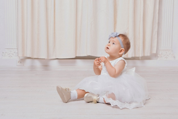 A little girl in a dress sits on the floor on a white background. child promotes children's clothes Premium Photo