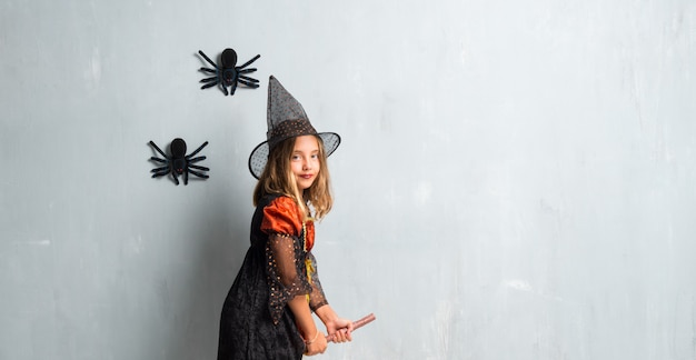 Little girl dressed as a witch for halloween holidays above on the broom and flying Premium Photo