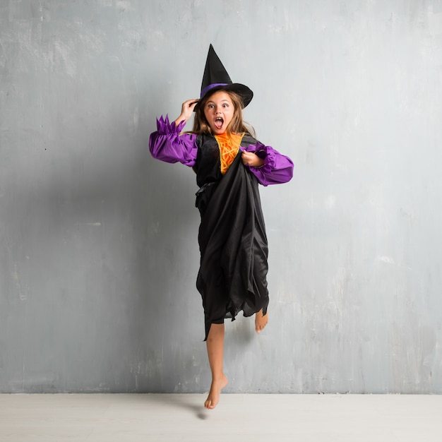 Little girl dressed as a witch for halloween holidays and jumping Premium Photo