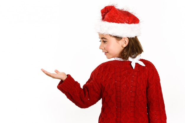 Little girl dressed in santa claus with a raised hand Free Photo