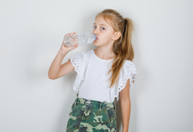 Little girl drinking water in white t-shirt, skirt and looking thirsty Free Photo
