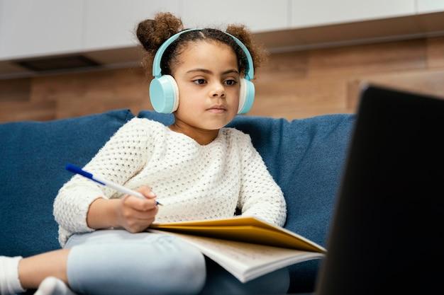 노트북 및 헤드폰 온라인 학교 동안 어린 소녀 무료 사진