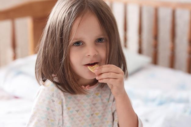 ベッドに座ってクラッカースナックを食べる少女 Premium写真