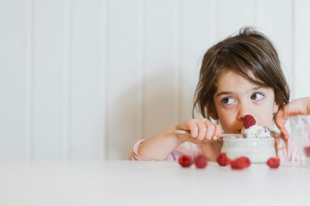 Little girl eating fresh raspberry with cream Free Photo