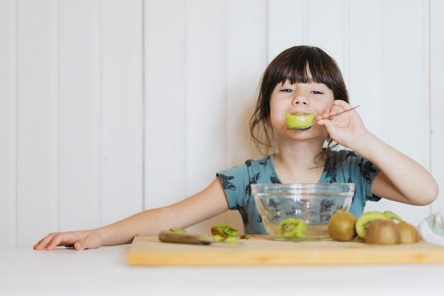 Little girl eating kiwifruit Free Photo