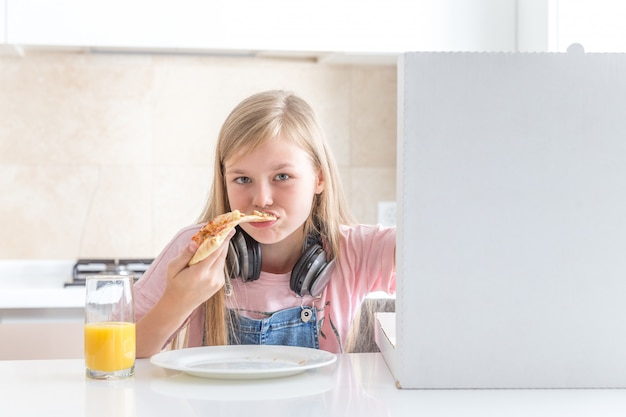 Little girl eating pizza sitting at the table Premium Photo
