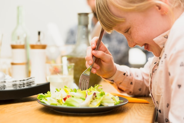 Little girl eating tasty dish Free Photo