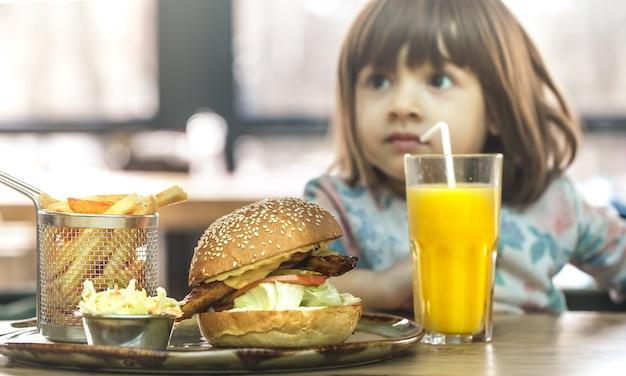 어린 소녀는 패스트 푸드 카페에서 먹는 무료 사진