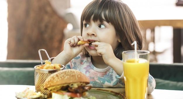 小さな女の子がファーストフードカフェで食べる 無料写真