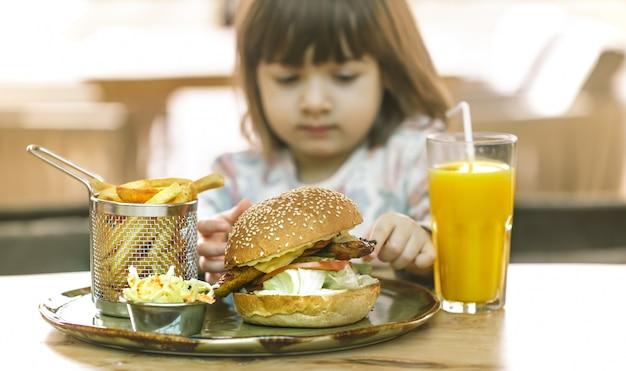 어린 소녀는 패스트 푸드 카페에서 먹는 프리미엄 사진