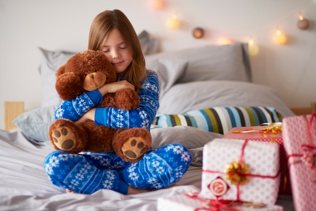 Little girl embracing teddy bear at christmas Free Photo