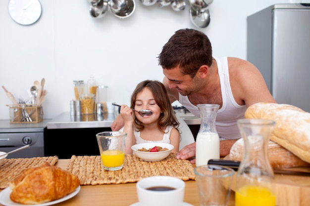 Little girl enjoying her breakfast with her father Premium Photo