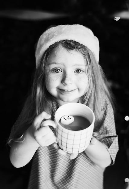 Little girl enjoying a mug of hot chocolate Free Photo