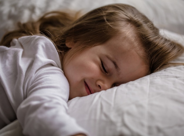 Little girl falls asleep in bed on white pillow Free Photo
