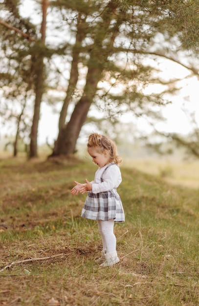 Little girl in the forest. on a forest road among the pines. Free Photo