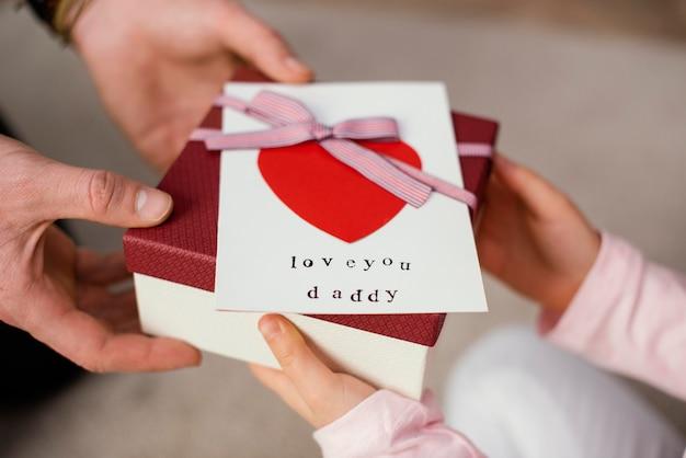 그녀의 아버지에게 아버지의 날 선물 상자를주는 어린 소녀 무료 사진