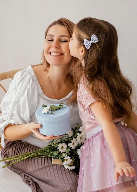 어머니의 날에 그녀의 엄마에게 봄 꽃과 선물 상자를주는 어린 소녀 무료 사진