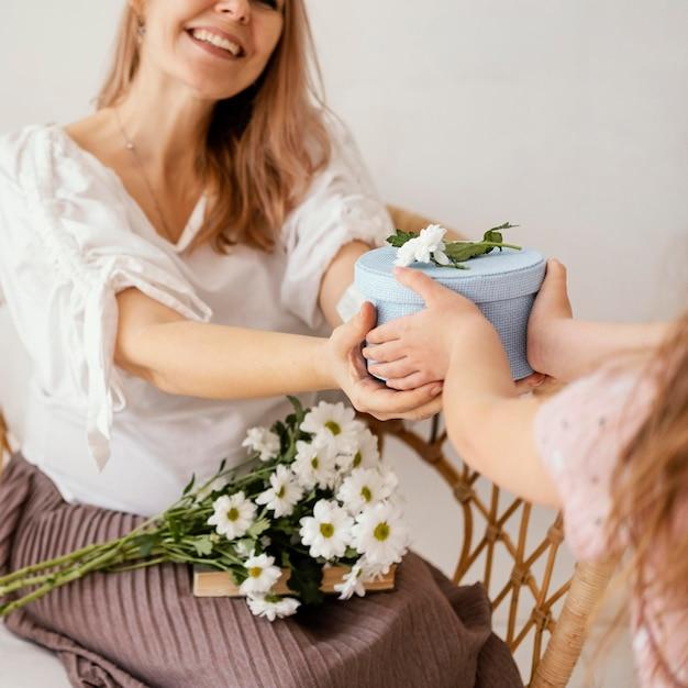 엄마에게 봄 꽃과 선물 상자를주는 어린 소녀 무료 사진
