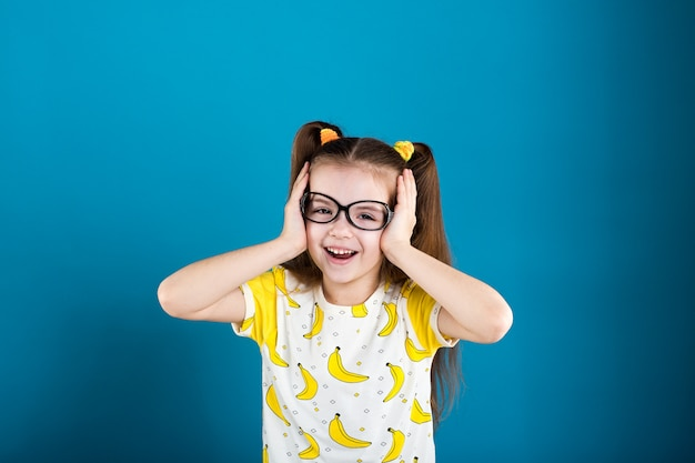 Little girl in glasses and banana t-shirt on blue background Premium Photo