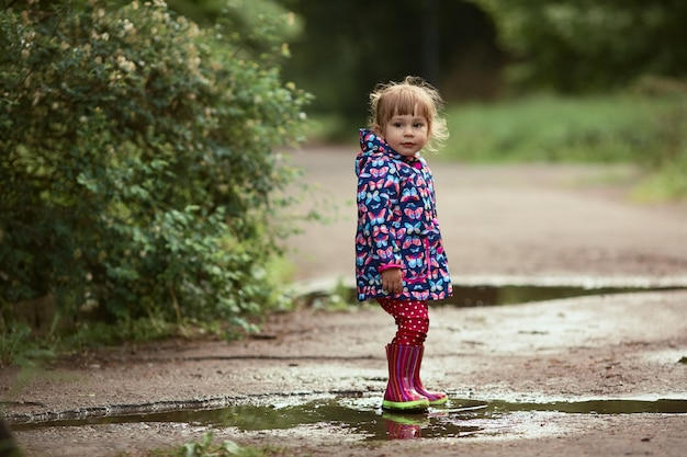 Little girl in gumboots has fun walking in the pools after the rain Free Photo