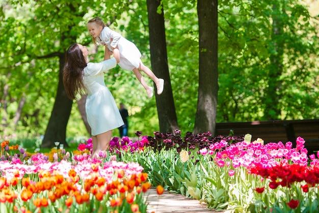 Little girl and happy mother enjoying warm day in bloomig tulip garden Premium Photo