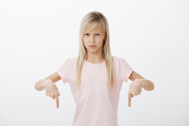 Маленькая девочка ненавидит мыть посуду. портрет недовольной отталкивающей симпатичной молодой дочери со светлыми волосами, указывающей вниз и хмурящейся, обиженной, выражающей неприязнь и раздражение над серой стеной Бесплатные Фотографии