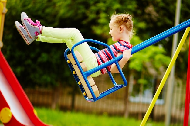 Little girl having fun on a swing outdoor Free Photo